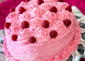 Raspberry cake is an almond scented white cake layered with raspberry buttercream and raspberry jam, with no artificial coloring. The perfect cake to celebrate any special occasion, especially Valentine's Day! Recipe shared with permission granted by Lucy Burdette, author of Fatal Reservations.
