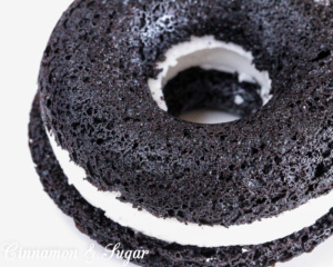 Black-and-Whites Baked Donuts are rich, super chocolately donuts with a creamy filling, reminiscent of everyone's favorite chocolate sandwich cookies.