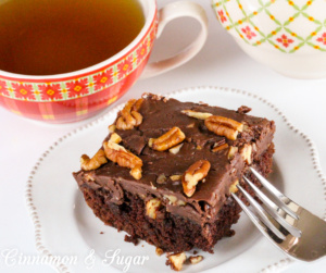 Spanish Chocolate Cake is a rich chocolate cake that is topped with a fudgy, pecan-laden frosting. A hint of warm cinnamon makes this a special dessert. Recipe from S.C. Perkins, author of MURDER ONCE REMOVED.