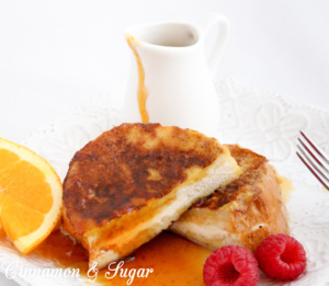 Stuffed French Toast are slices of French bread stuffed with orange zest and cream cheese. Paired with Honey Orange Syrup makes it a perfect breakfast! Recipe shared with permission granted by Kate Carlisle, author of THE BOOK SUPREMACY.