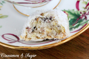 Cranberry Walnut Cookie Balls combine the crunch of walnuts in a shortbread-style cookie along with the tart sweetness of cranberries. Rolled in fluffy powdered sugar, these are a welcome addition to any holiday cookie platter. Recipe shared with permission granted by Meg Macy, author of HAVE YOURSELF A BEARY LITTLE MURDER.