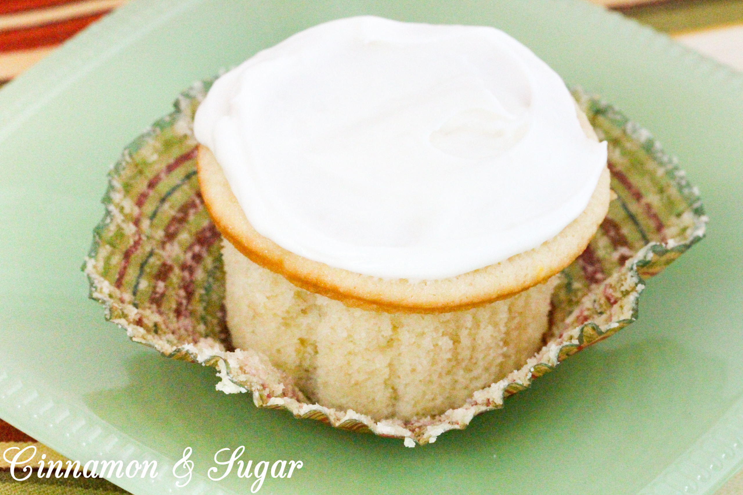 Lemony cream cheese frosting tops little lemon cakes that are super moist thanks to a generous dollop of sour cream. Perfect for afternoon tea or brunch! Recipe shared with permission granted by Maureen Klovers, author of MURDER IN THE MOONSHINE.
