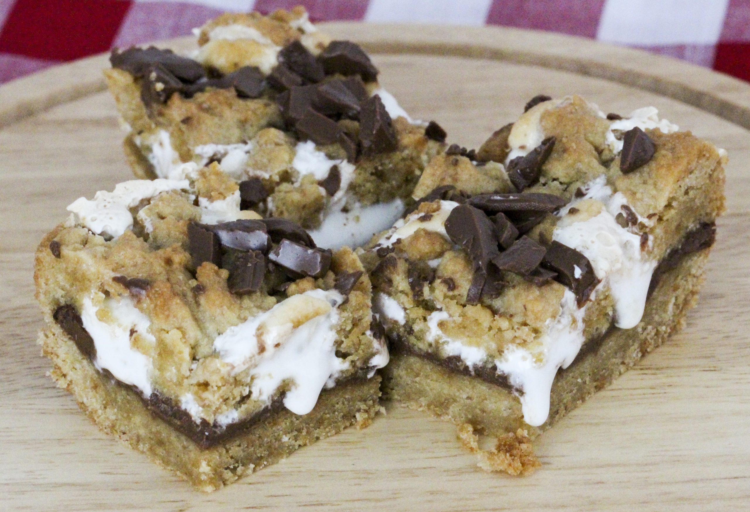 No campfires required! S'mores Cookie Bars have a graham cracker cookie dough base and topping, and a rich layer of iconic chocolate bars with gooey marshmallows. Recipe created by Cinnamon & Sugar for Catherine Bruns, author of KNEE DEEP IN DOUGH.