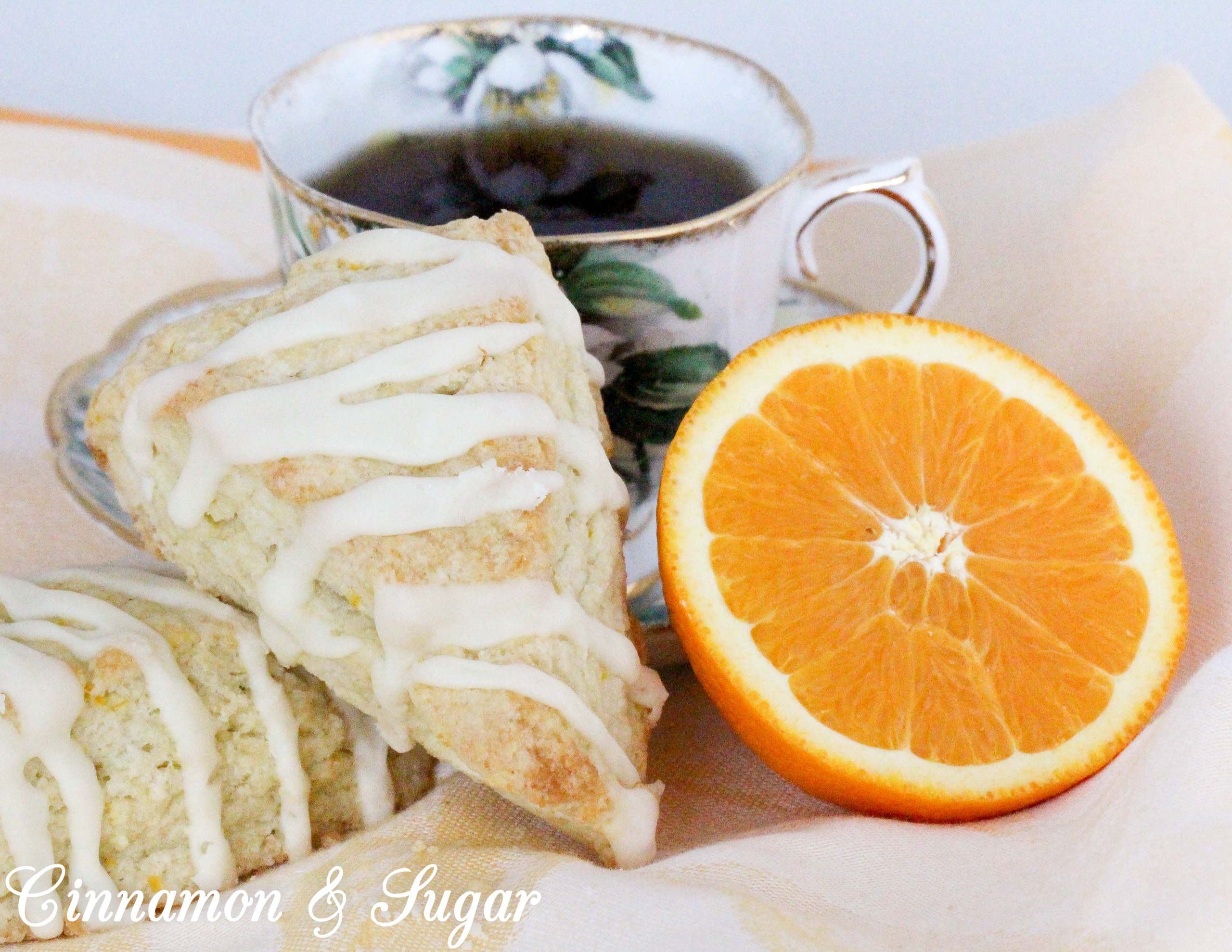 These flaky Orange Scones are easy to mix up and the sweet, orange glaze boosts the wow factor. Scrumptious on their own, a smear of orange marmalade would make them even more delectable! Recipe shared with permission granted by Maddie Day, author of NACHO AVERAGE MURDER.