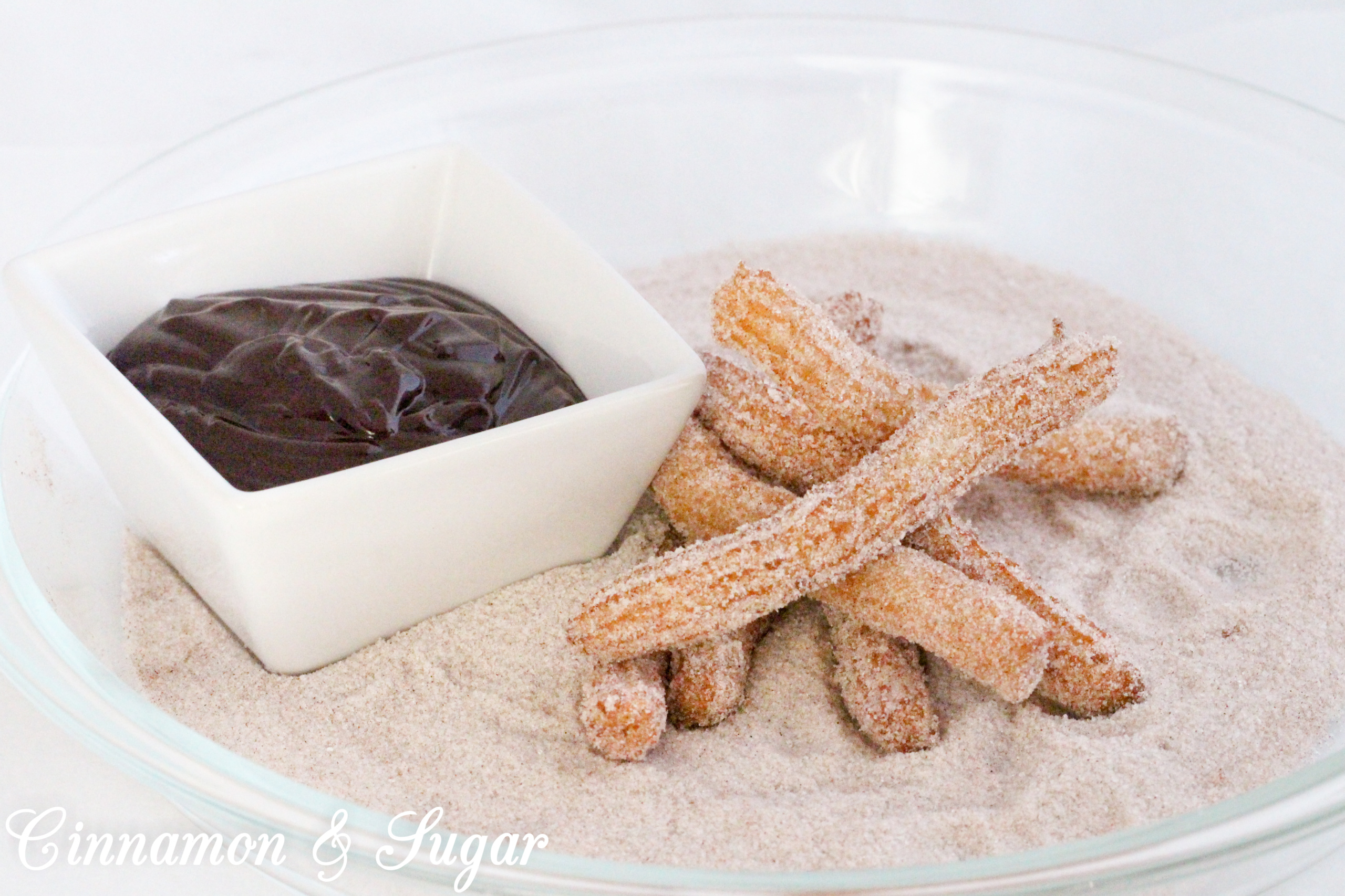 It's not that difficult to make fresh, hot from the skillet, churros. Rolled in cinnamon and sugar, and then served with warm Mexican chocolate dipping sauce, this dessert is a scrumptious treat! Recipe shared with permission granted by S.C. Perkins, author of LINEAGE MOST LETHAL.