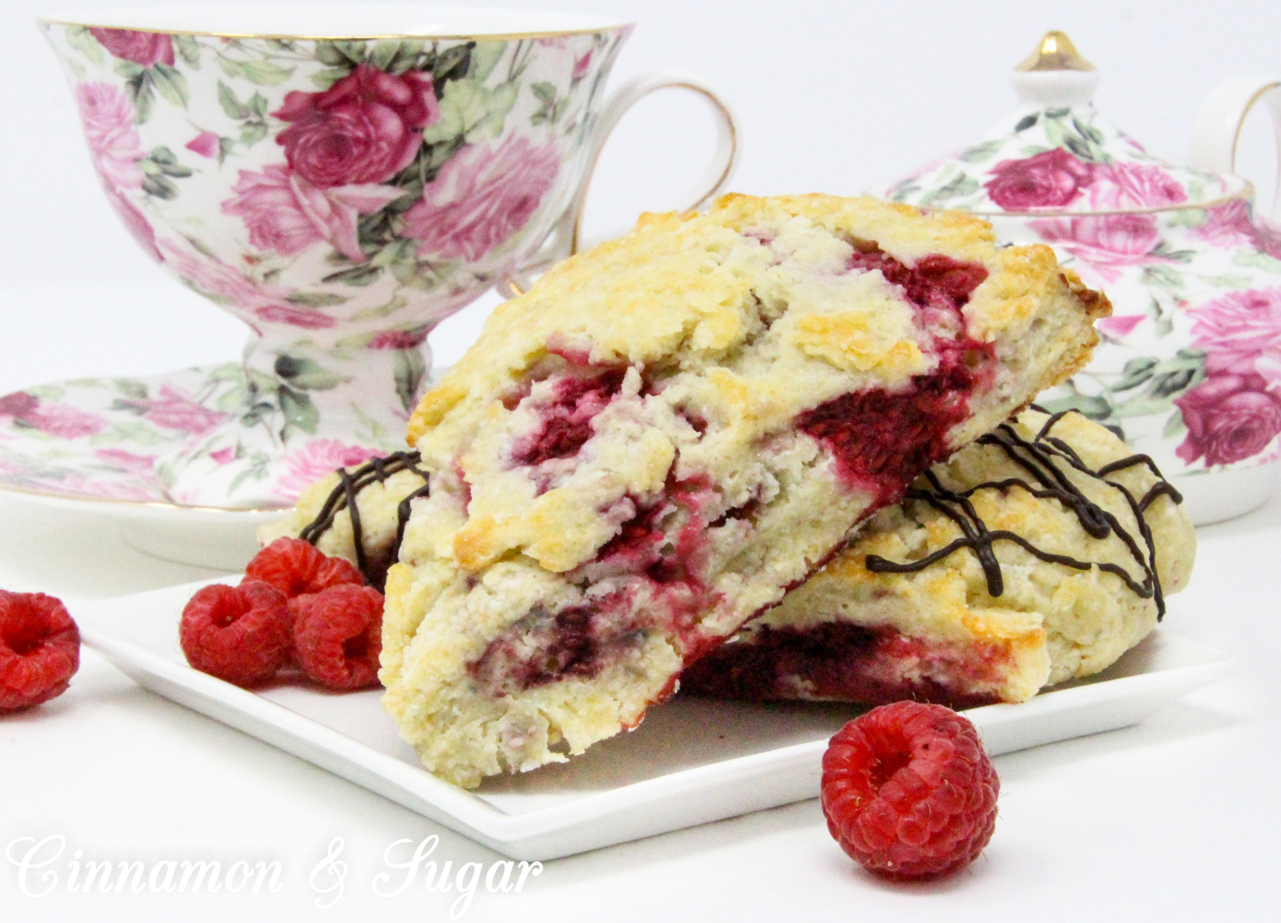Raspberry Scones with Dark Chocolate Drizzle are rich, flaky, and flavorful, thanks to the addition of lemon oil and lemon peel, plus loads of raspberries. Drizzled with dark chocolate, the results are a scrumptious combination!