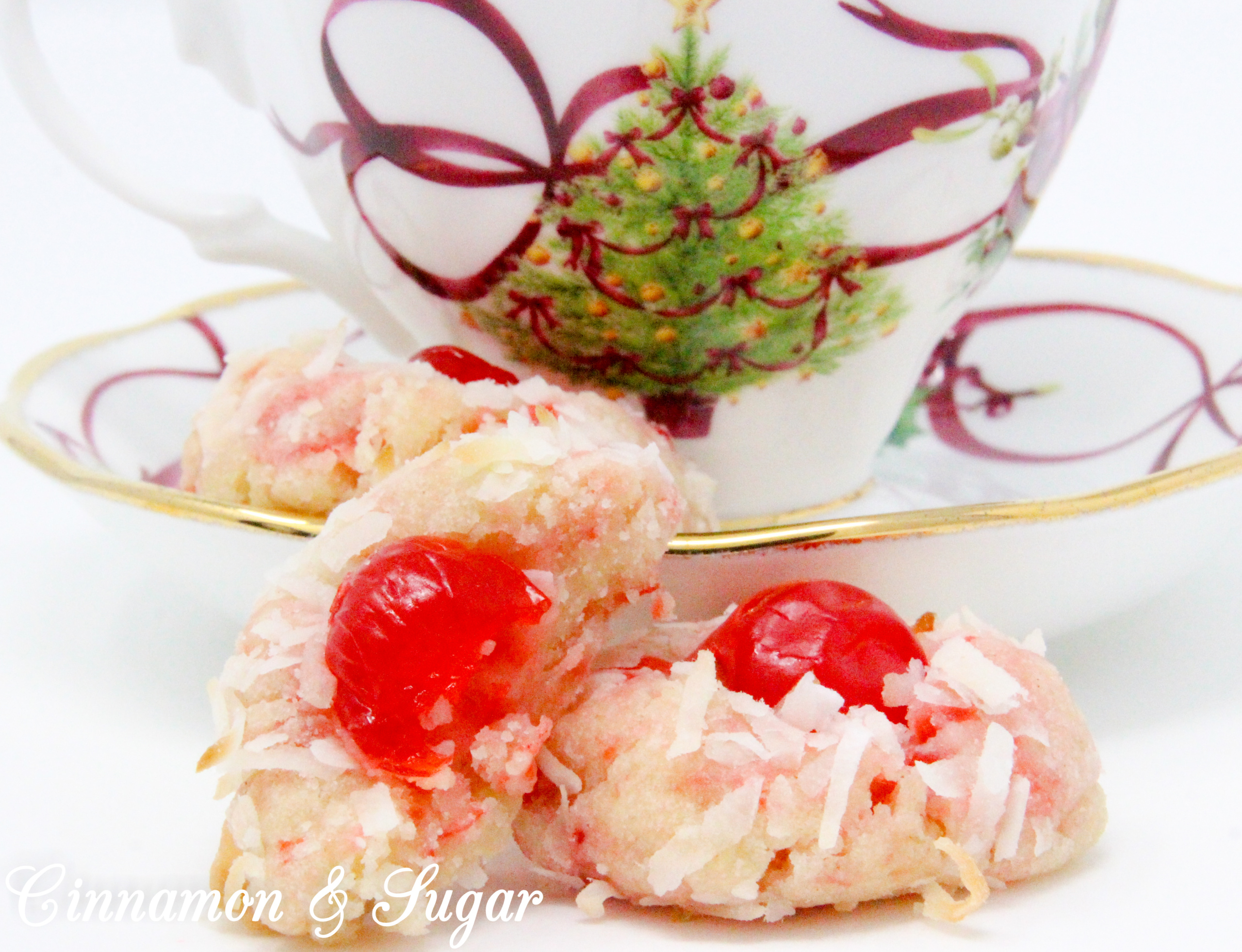 With snowy white coconut and glistening red cherries, shortbread-style Yuletide Coconut Cherry Cookies add holiday cheer to Christmas cookie platters. Recipe created by Cinnamon & Sugar for Deborah Garner, author of YULETIDE AT MOONGLOW.